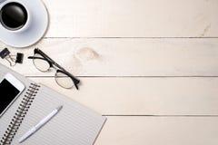 Плоское положение личных аксессуаров офиса, компьтер-книжки, тетради, кофейной чашки и камеры на деревянной предпосылке, взгляд с Стоковые Изображения