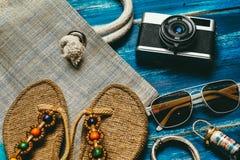 Плоское положение моды лета с солнечными очками тапочек камеры и другими аксессуарами девушки на голубой деревянной предпосылке Стоковые Фото