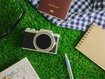 Плоское положение путешествуя аксессуары на предпосылке зеленых трав с космосом экземпляра стоковое фото