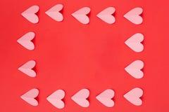 Плоское положение розовых бумажных сердец аранжировало как рамка на красной предпосылке стоковое фото rf