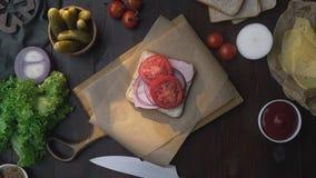 Плоское положение сэндвича с отрезанными ветчиной и овощами на деревянной доске в луче света, рукой шеф-повара добавляет видеоматериал