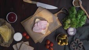 Плоское положение сэндвича с отрезанными ветчиной и овощами на деревянной доске в луче света, рукой шеф-повара добавляет лук видеоматериал