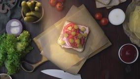Плоское положение сэндвича с отрезанными ветчиной, соленьем и овощами на деревянной доске в луче света, делая  акции видеоматериалы
