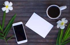 Плоское положение с белой бумагой и бамбуком выходит на деревянную предпосылку Стоковое Фото