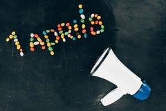 плоское положение с громкоговорителем и конфетами аранжировало в помечать буквами 1 апрелей стоковые фото