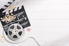 плоское положение с нумератором с хлопушкой, filmstrips, попкорном и ретро билетами кино аранжировало на белой деревянной столешн стоковые фотографии rf