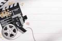 плоское положение с нумератором с хлопушкой, filmstrips, ретро камерой и билетами кино аранжировало на белой деревянной поверхнос стоковые изображения