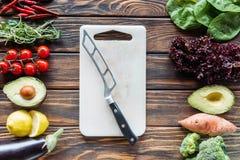 плоское положение с разделочной доской с ножом и свежими овощами аранжировало вокруг стоковые фото