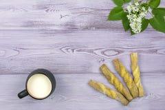 Плоское положение черная кружка молока Домодельные сладостные печенья Sprig и белая сирень цветут на таблице Стоковое Фото