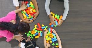 Плоское положенное видео сцены азиатского учителя играет красочные блоки строения забавляется с азиатскими студентами совместно сток-видео