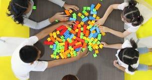 Плоское положенное видео сцены азиатского учителя играя красочные блоки строения забавляется с азиатским студентом совместно, видеоматериал