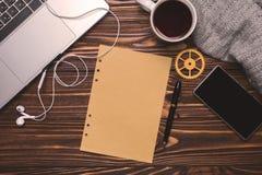Плоское рабочее место офиса положения Компьтер-книжка, чашка, наушники, телефон, шестерня, ручка, бумага Стоковое Изображение RF