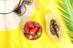 Плоское расположение положения стекла солнечных очков шляпы высокорослого с свежими тропическими лист ладони клубник папапайи фру стоковое фото