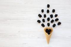 Плоск-положение конуса мороженого waffle сладостного с ежевиками на белой деревянной предпосылке Стоковое Изображение RF
