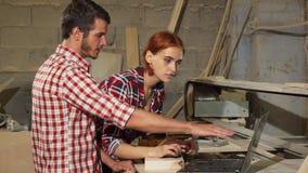 2 плотника используя ноутбук на их мастерской пока делающ мебель акции видеоматериалы