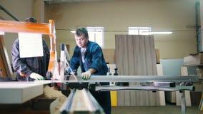 Плотники работников режут деревянную доску на электрической пиле на фабрике мебели акции видеоматериалы