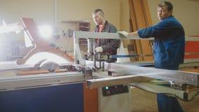 Плотники работников режут деревянную доску на электрической пиле на фабрике мебели стоковое изображение