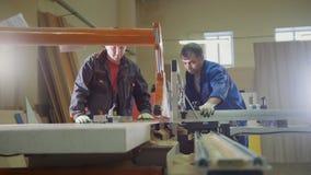 Плотники работников режут деревянную доску на электрической пиле на фабрике мебели стоковое фото