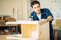 Плотник бить молотком ноготь молотком в деревянную доску стоковое фото