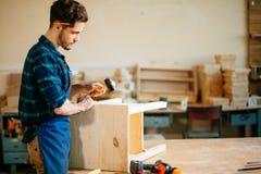 Плотник бить молотком ноготь молотком в деревянную доску стоковое фото rf