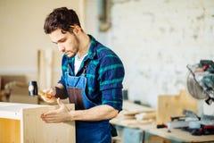 Плотник бить молотком ноготь молотком в деревянную доску стоковые изображения