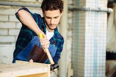 Плотник бить молотком ноготь молотком в деревянную доску стоковые фото