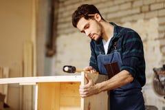Плотник бить молотком ноготь молотком в деревянную доску стоковое изображение rf