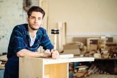 Плотник бить молотком ноготь молотком в деревянную доску стоковое изображение