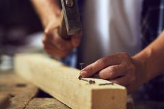 Плотник бить молотком ноготь молотком в деревянную планку в его мастерской стоковое фото rf