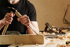 Плотник высекая древесину с зубилом стоковое изображение
