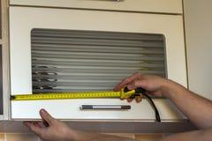 Плотник в мастерской делает измерения продукта с измеряя рулеткой Плотник использует метр во время работы Стоковые Фотографии RF
