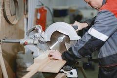 Плотник в форме работает на инструменте ` s плотника для резать древесину Стоковое Изображение