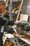 Плотник, в форме, работает при токарный станок отрезая бар древесины Стоковые Изображения RF