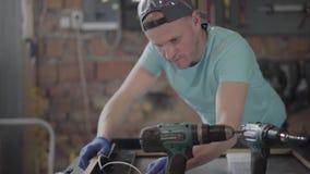 Плотник в черной установке крышки и перчаток крепит на клею деревянная рамка Человек используя оружие клея силикона в мебели сток-видео