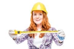 плотник девушки на белой предпосылке с рулеткой в руке Стоковая Фотография RF