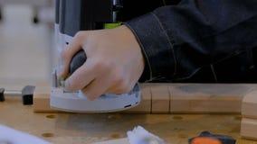 Плотник используя электрический шлифовальный прибор для того чтобы отполировать древесину сток-видео