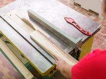 Плотник пилит луч тимберса на круглой пиле Стоковое Изображение