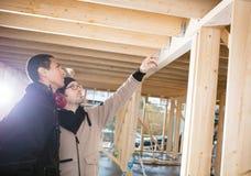 Плотник показывая деревянные балки к коллеге на месте Стоковая Фотография