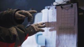 Плотник работника в мастерской joinery проверяя информацию плана на круглой пиле бумаги перед использованием Стоковое Изображение RF