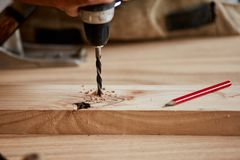 Плотник сверлит отверстие с электрическим сверлом стоковые фото