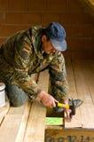 Плотник строя новый пол комнаты просторной квартиры стоковая фотография