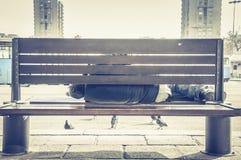 Плохие бездомные человек или беженец спать на деревянной скамье на городской улице в городе, социальная репортажно-документальная стоковая фотография