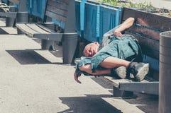 Плохие бездомные человек или беженец спать на деревянной скамье на городской улице в городе, социальная репортажно-документальная стоковая фотография rf