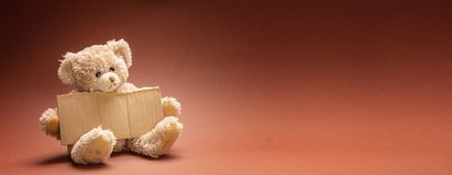 Плохой бездомный умолять ребенка Плюшевый мишка грустная, держащ пустой знак картона стоковые изображения
