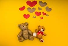 2 плюшевого мишки на желтых предпосылке и сердце над ними стоковая фотография rf