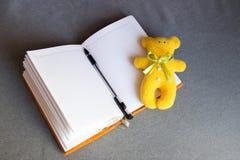 Плюшевый медвежонок и открытые тетрадь и ручка Стоковое фото RF
