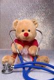 Плюшевый медвежонок и стетоскоп на белой предпосылке Стоковая Фотография RF