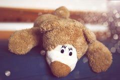 Плюшевый медвежонок лежа на кровати Стоковое Изображение