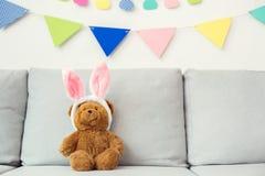 Плюшевый медвежонок сидя на софе в предпосылке ушей зайчика яркой стоковое фото