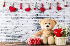 Плюшевый медвежонок сидя с подарочной коробкой и красным сердцем сформировал Стоковое Изображение RF
